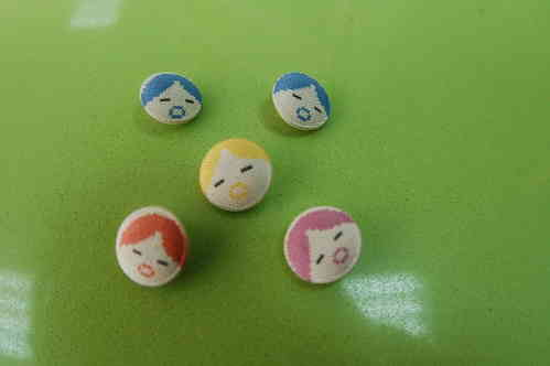 Lined buttons with cloth. Faces of dolls