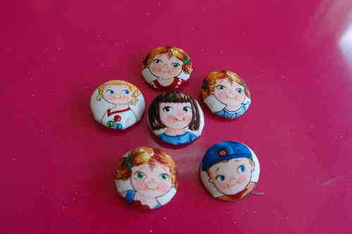 Lined buttons with cloth. Cutted faces of dolls